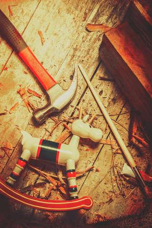 menuisier: Toy artisanat dans la création sur le bureau d'un petit assistant santas avec un modèle rennes en bois dans les étapes finales de la production. Vintage christmas background Banque d'images