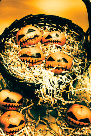 picknic: Basket of little halloween horrors with tiny evil pumpkin heads made from citrus fruits