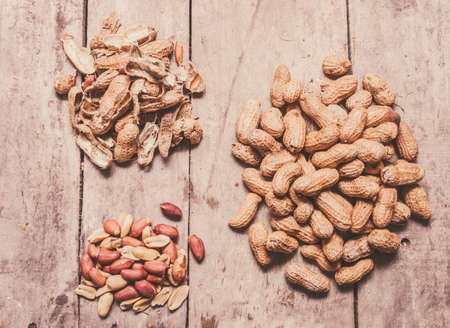 shelling: Shelling in process with a pile of shelled and unshelled peanuts on country kitchen bench. Nut preparation Stock Photo