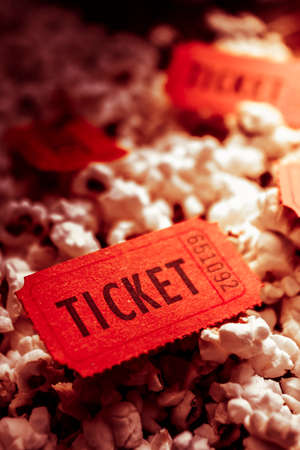 popped: Close Up of Red Numbered Tickets on Top of Freshly Popped Movie Popcorn. Theatre and Festival Events