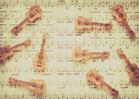 ornately: Classical rhythm art on scattered old string instruments placed ornately on lined music chart. Vintage guitar music