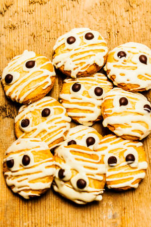 mummified: Scared little mummified monster cookies piled on old rustic kitchen bench. Halloween baking treats