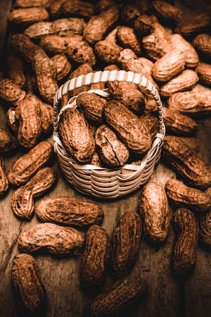 monkey nut: Dried whole peanuts, groundnuts, goobers, monkey nuts in their seedpods or shells with a small full wicker basket and vignette