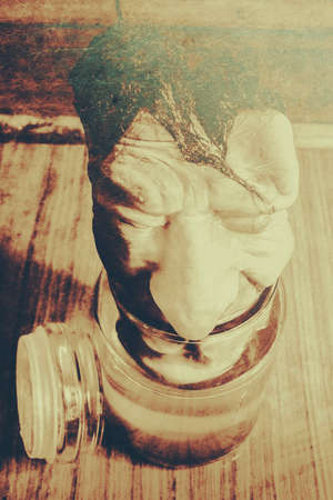 horrifying: Strange vintage horror scene with a masked face rising from halloween horror jar. Pickle me grandfather