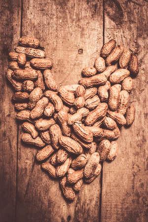 forme et sante: gros plan rustique des arachides formant forme de coeur sur la cuisine en bois banc. la santé du c?ur et des noix