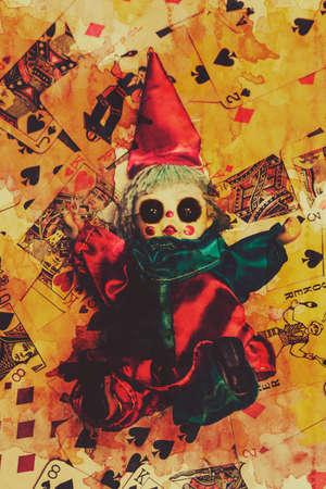 joker card: Demonic possessed Joker doll on a blood splattered background of playing cards. Evil dolls Stock Photo