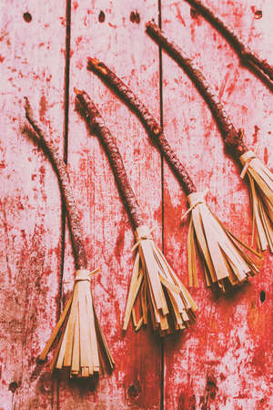broomsticks: Creative red splattered witch broomsticks on a rustic wood background. Gathering of evil witches