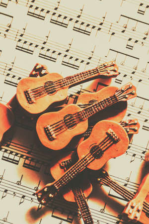 accoustic: Vintage music accoustic still life on pile of brown ceramic guitars on music sheet