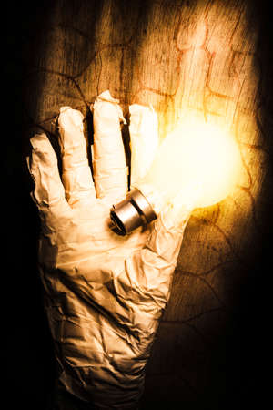 grisly: Halloween ideas concept with a shining light bulb in a crinkled mummy hand over textured wood Stock Photo