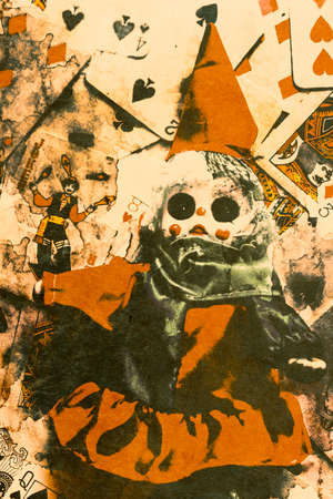 messed: Creepy vintage carnival clown doll messed up on a pile of black magic playing cards. Evil tricks