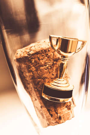Cork and gold trophy floating in a flute of champagne, resembling achievement and success symbol celebrating a win or happy event