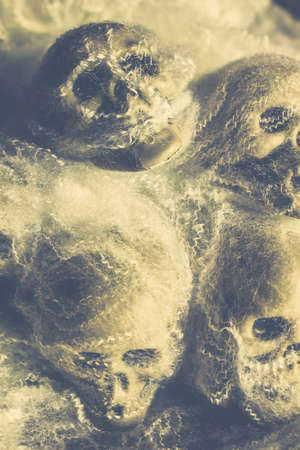merciless: Retro styled poster artwork on four eerie horror skeleton heads decomposing in funnels of death. The spiders torture chamber