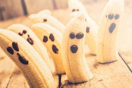 jilted: Ghostly banana monsters with choc face details sliding in haunted halloween scene. Spooky seasonal snacks Stock Photo