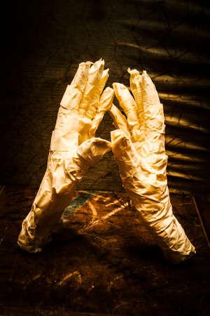 mummification: Dark sinister scene of two severed mummy hands fighting in a horror arm wrestle. Halloween fight night Stock Photo
