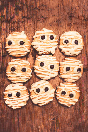 kooky: Frightening kitchen foods with mummy white choc short-bread decorations looking fearful on wooden backdrop. Halloween themed food