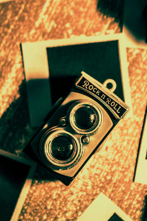 bygone: Old toy camera placed on a blank retro travel photo in a flashback to obsolete film. Bygone photograph still