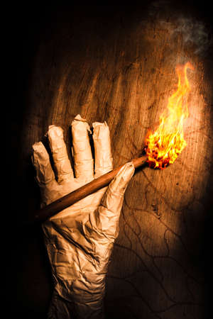 cursed: Hand of a historic horror mummy holding a torch flame in a dark cursed tomb. Rise of the dead mummy