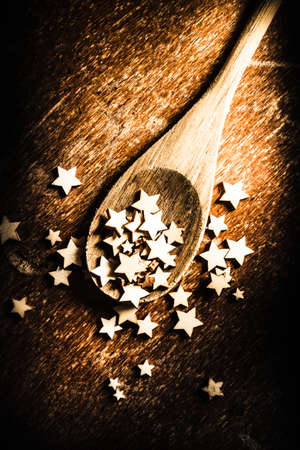 food still: Creative christmas food still life photo on a wooden spoon scooping a twinkle of wooden stars