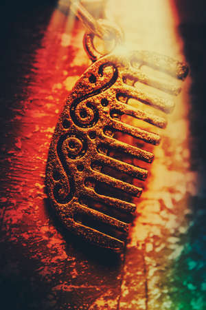 beautification: Vintage still life of a Egyptian gold comb shimmering in golden light of ancient beauty. History of beautification
