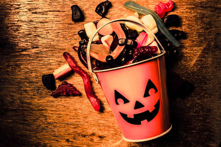 Eerie holiday background on a halloween pumpkin can tipped over in all you can eat view from above. Sugar high Stock Photo
