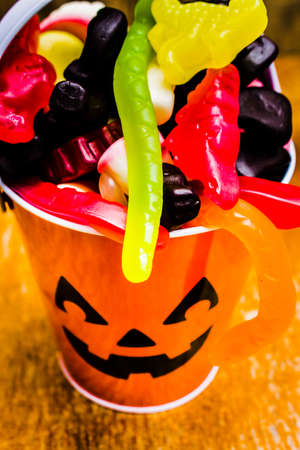 Colourful decorative still life on a kids pumpkin bucket filled with delicious trick or treat lollies. Halloween party details Stock Photo