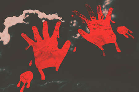 background csi: Eerie dark background on two red bloody hand prints blotched on the inside of a house window. Trace of a serial killer Stock Photo