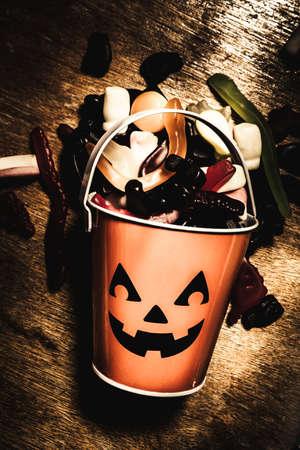 Cute dark halloween scene of a jack o lantern candy collector tin scattered in fun seasonal style. Fall of Halloween