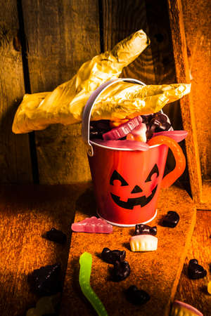 chewy: Creepy halloween still life photo on a invisible mummy collecting a Jack o Lantern candy bucket overfilled with chewy lollies Stock Photo