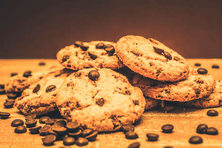 speckled wood: Delicious sweet baked biscuits with a still life stack on chocolate chip cookies on country wood kitchen bench speckled with cooking choc drops Stock Photo