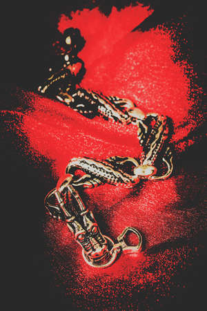 fine art: Fine art jewellery photo on a precious metal sterling silver dragon bracket on red fabric background. Treasures from the Asian silk road