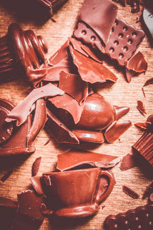 moulded: Chocolate in destruction with a crash of smashed chocolate in a morning tea demolition with moulded chocolate dessert shapes. Tea break Stock Photo