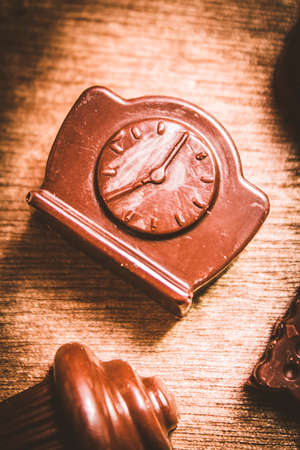 suger: Cute food photography on a ticking chocolate clock on wooden bakery bench. Afternoon tea time