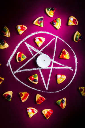 black magic: Black magic in practise with a occult satanic symbol into pizza sacrifice on purple background