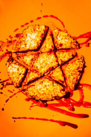 cursed: Object photography on a pentagram cut into a cheese and tomato pizza. Satanic snack Stock Photo