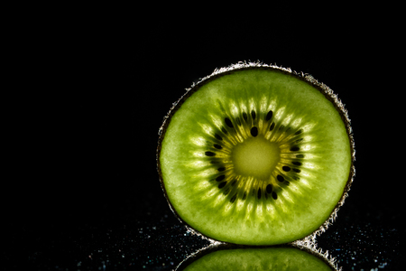 Healthy sliced kiwi fruit on black backgroud close up