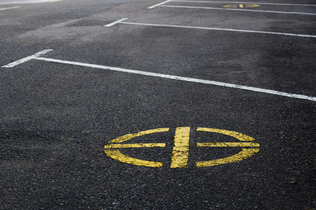 barring: Yellow road No parking sign marking of the circular shape on a background of asphalt.