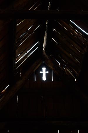 Light cross shape hole in dark room on old wood wall near roof.