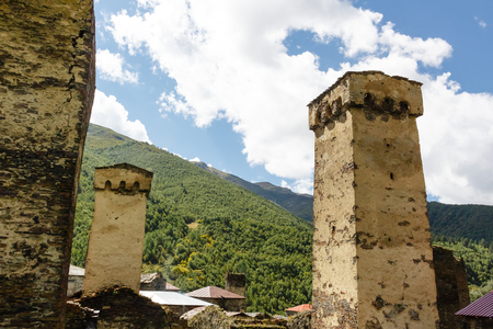 Old stone svan towers on street of Ushguli village in Svaneti, Georgia. Sunny day and sky with clouds background.