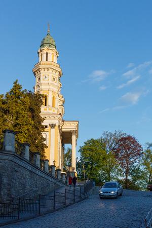 View of the church, trees, car and pair of people during sunset, blue sky, Uzhgorod, Zakarpattia region, Ukraine. Stock Photo