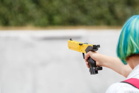 Girl with a yellow laser sport gun aims closeup 版權商用圖片