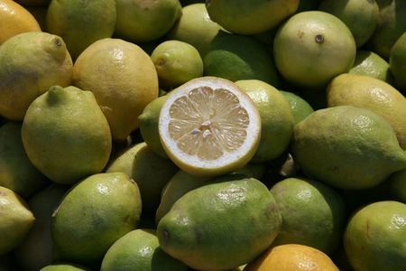 cut through: Background of green yellow lemons with one cut through on a food market in Chile