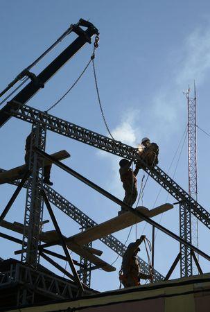 Bouwplaats in Ushuaia, Argentinië met onherkenbaar werknemers lassen een ijzeren frame van een gebouw.