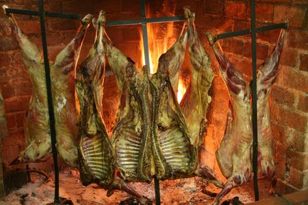 Sheep roasting near a fire in a typical Parilla restaurant in Patagonia.