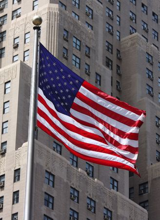American flag on a pole waving in the wind in front of brown NYC building Stock Photo - 3108282