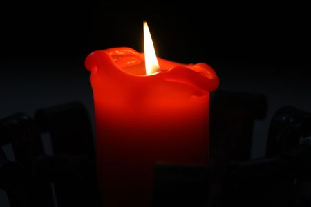 Close-up of a red candle burning in a dark church photo