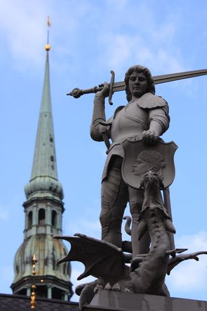 slaying: Statue of Saint George slaying the dragon and tower of Dome Church in Riga, Latvia Stock Photo