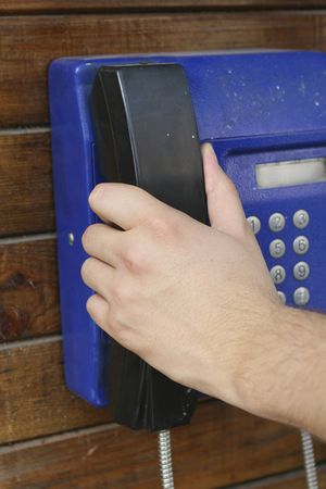 phone booth: Hand picking up the horn at a public phone booth