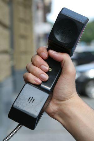 cabina telefonica: Una mano a la celebraci�n de la bocina de tel�fono p�blico en cabina telef�nica
