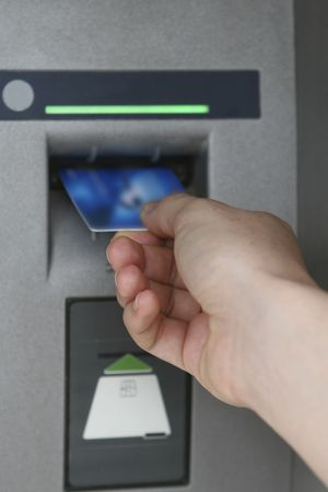 Hand inserting card in Automated Teller Machine (ATM) Stock Photo