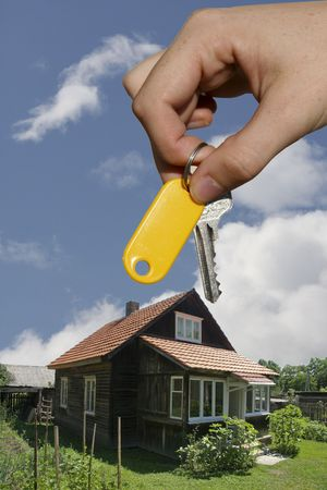 Hand holding a key in front of a house Stock Photo - 3397520